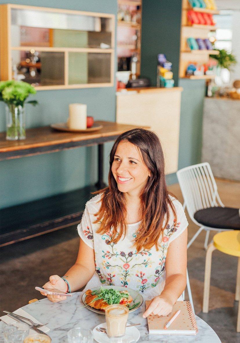 mujer sonriendo y comiendo en restaurante