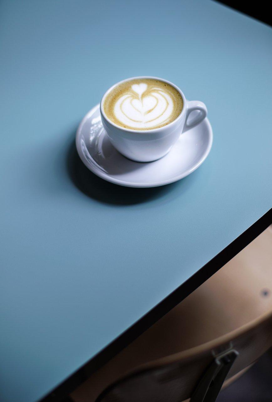 café con leche sobre mesa azul