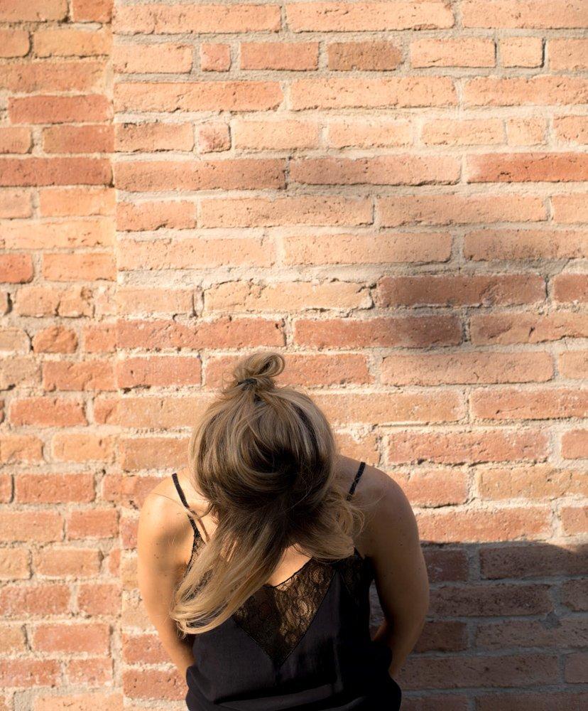 chica mirando hacia abajo en pared de ladrillo